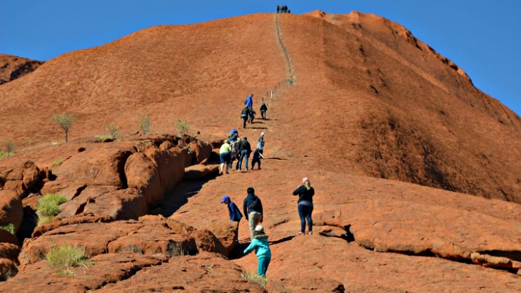 Tourists climb uluru banned