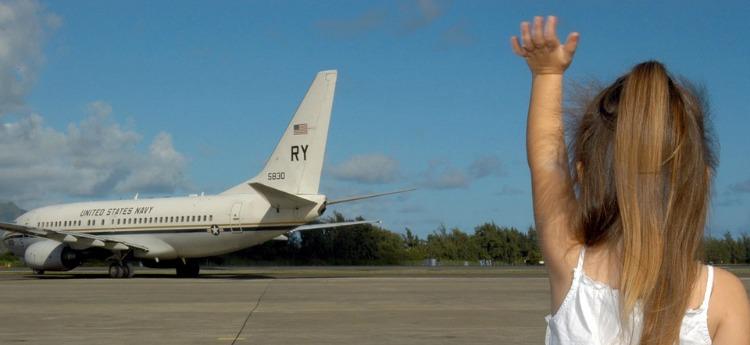 child waving to plane
