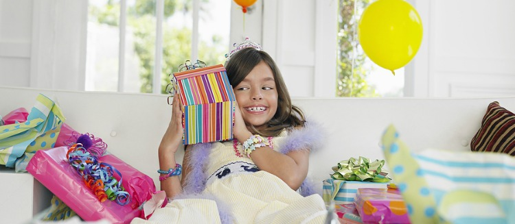 Cheerful young girl opening birthday presents in house