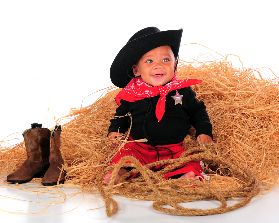 A happy biracial baby dressed as a cowboy sitting in a pile of hay. Isolated on white.