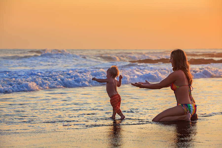 Family swimming fun in sea beach surf Happy mother baby son first step - toddler run to ocean wave on sunset sky background Child outdoor activity parent lifestyle summer holiday in tropical island ** Note: Soft Focus at 100%, best at smaller sizes