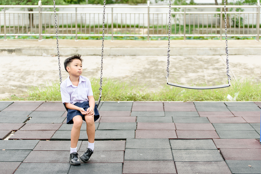 Young Thai student boy in school uniform sits and looks sad waiting for someone.