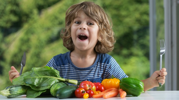 Cute little boy sitting at the table excited about vegetable meal bad or good eating habits nutrition and healthy eating showing emotions concept